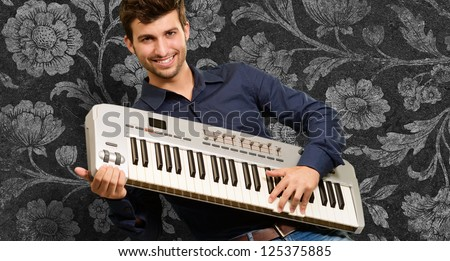 Young Man Holding Piano On Wallpaper