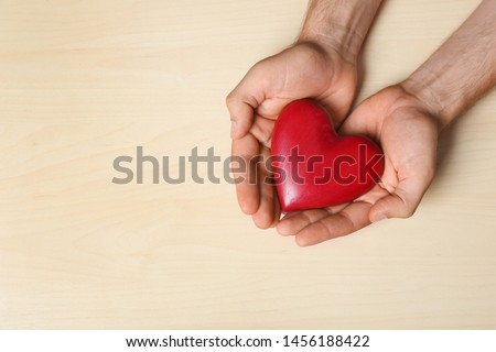 Young man holding red heart on light wooden background, top view with space for text. Donation concept