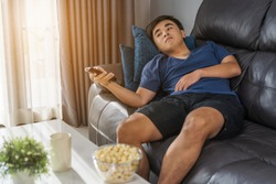 young man holding remote control and watching TV while sitting on sofa in the living room