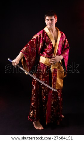 Young man holding samurai sword over dark background