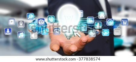 Young man holding shinny lightbulb in his hand with digital icons flying around