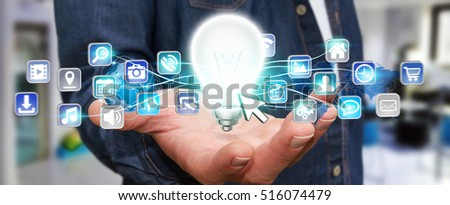 Young man holding shinny lightbulb in his hand with digital icons flying around 3D rendering