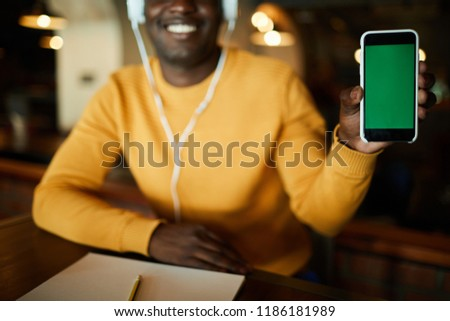 Young man holding smartphone in hand and showing you important notification or curious advert on its screen