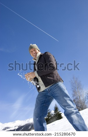 Young man holding snow ball in snow field, smiling, portrait, low angle view