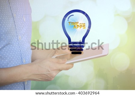 Young man holding tablet with SOLUTION text on light bulb