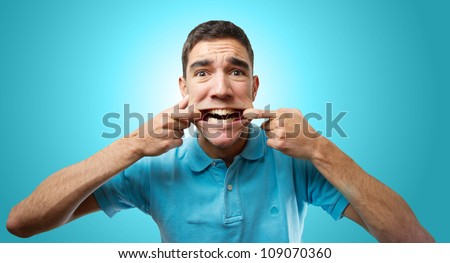 Young man holding the corner of his lips over light blue gradient background