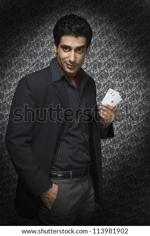 Young man holding three aces