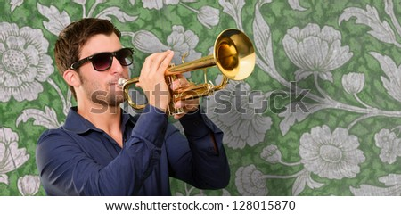 Young Man Holding Trumpet On Wallpaper