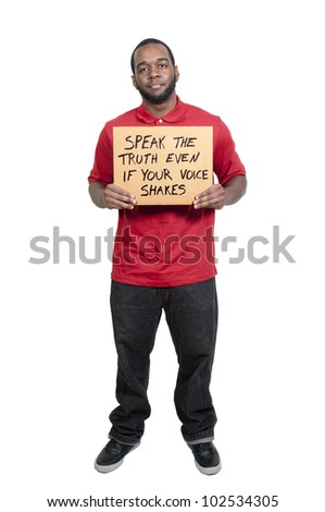 Young man holding up a sign that says Speak The Truth Even If Your Voice Shakes