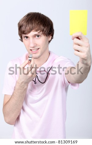 Young man holding up a yellow card and blowing his whistle