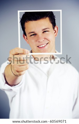 Young man holding up an image of himself