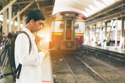 Young man holding using phone with backpack standing on platform at train station - travel concept,copy space.