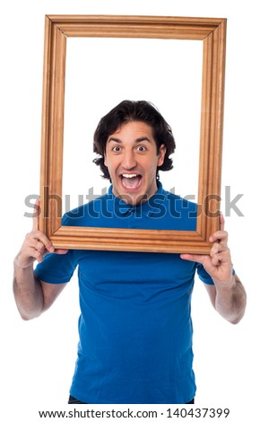 Young man holding wooden frame around his face