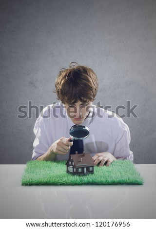 Young man holds a magnifying glass over a miniature house.
