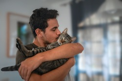 young man holds a tabby cat in his arms and kisses it
