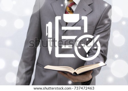 Young man holds book with checklist clock check mark pen icon on a virtual screen. Compliance Business Learning Time Management Work Planning Regulations concept.