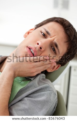 Young man holds his mouth in pain