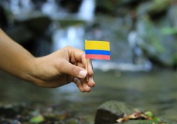 Young man holds national flag of Colombia on wooden stick. Teenager gives respect to nation state of Colombia. Stream and beauty of nature in background. Concept of humanity and prosperity.