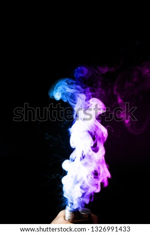 Young man holds vape in his hand. Vape clouds splash from vape coil on black background. Fog is dual color — blue and purple. Stock isolated colorful smoke with spray boiling glycerine.