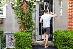 Young man, house, entering outdoor spring garden with hanging plant flowers covering brick wall in backyard porch of home by door, insect mosquito pest net