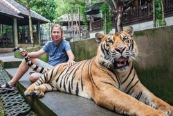 Young man hugging a big tiger in Thailand