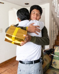 young man hugging his dad while giving him a father's day gift
