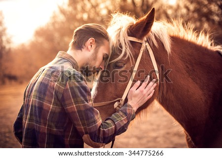 Young man hugs a horse. Autumn outdoors scene