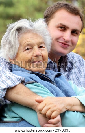 Young man hugs elderly woman. Focus on woman.