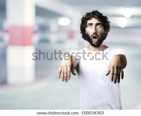 young man imitating a zombie against a garage background - stock photo