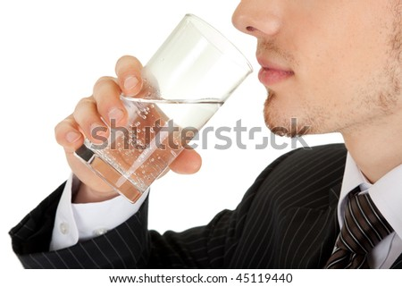 young man in a black business suit holds a glass of water on a white background