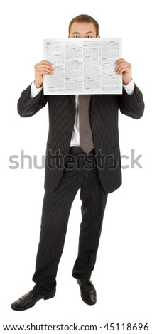 young man in a black business suit reads the newspaper on a white background