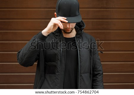 young man in a black fashionable baseball cap and a winter warm jacket posing on the street #754862704