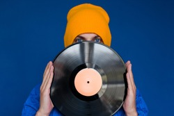 young man in a blue sport 90s style jacket and yellow hat holding vinyl record, man hides his face under vinyl disc