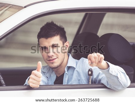 young man in a car showing his car keys