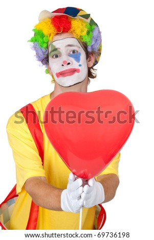 Young man in a clown's costume holding a heart-shaped balloon - isolated