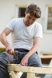 Young man in a diy project outside hammering a nail into a wooden structure while building a playhouse.