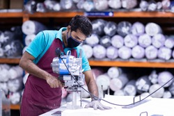 Young man in a face mask and protective chain gloves at work. Man with cutter machine and personal protective equipment at garment industrial work place. Fabric cutter in Asian textile garment factory