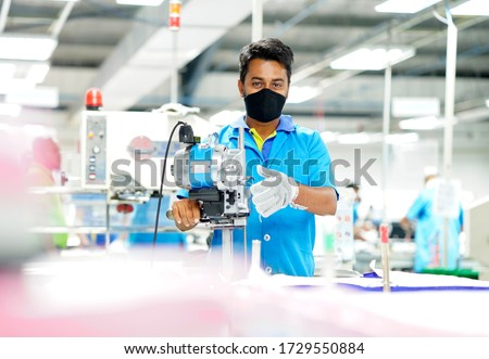 Young man in a face mask and protective chain gloves at work. Man with cutter machine and personal protective equipment at garment industrial work place. Fabric cutter in Asian textile garment factory Foto stock ©