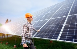 Young man in a helmet with a tablet in his hands stands near the solar panels. Green ecological power energy generation. Solar station development concept. Home construction.