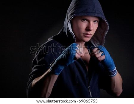 Young man in a hood on black background