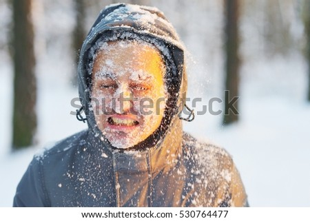 Young man in a hooded jacket with his eyes closed covered in snow during a walk in the winter woods at sunset. Concept of sport and a healthy lifestyle.