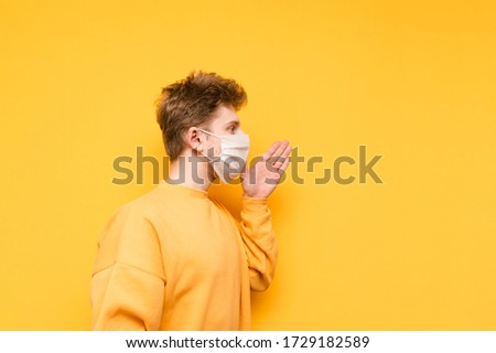 Young man in a medical mask shouts to the side with his hand to his face on a yellow background. Guy in the protective white mask is talking. Coronavirus pandemic. COVID-19. Quarantine.