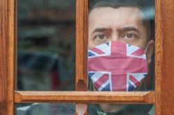 Young man in a protective mask with a British flag stays at home looking out the window. Lockdown in the UK. Corona virus mutated covid-19. Strengthening quarantine. Coronavirus is mutating. Health