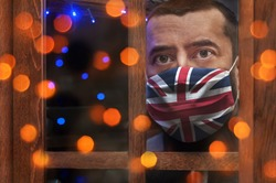 Young man in a protective mask with a British flag stays at home looking out window. Lockdown in the UK. Corona virus mutated covid-19. Strengthening quarantine. Coronavirus is mutating. Health. Bokeh