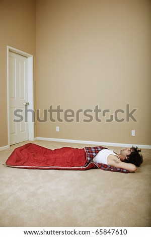 Young man in a sleeping bag in empty room