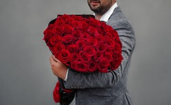 Young man in a suit holds a large bouquet of red roses on his shoulder, clenching his fist like a macho, because he wants to propose to his girlfriend.