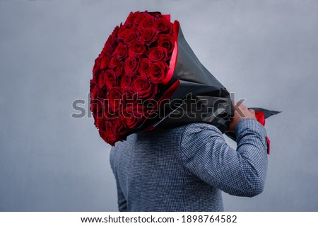Young man in a suit holds a large bouquet of red roses on his shoulder, clenching his fist like a macho, because he wants to propose to his girlfriend. Foto d'archivio ©