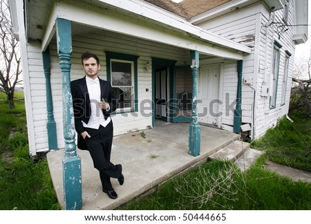 Young man in a tuxedo standing on front of an abandoned house.