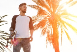 Young man in a white blank long sleeve t-shirt holding skateboard is looking aside while standing in the skate park on a warm sunny background. A skater is standing on the palm tree background.