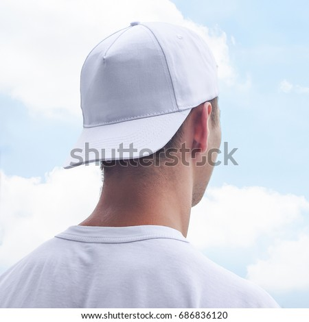 Young man in a white cap and t-shirt. White baseball cap mockup. Close-up